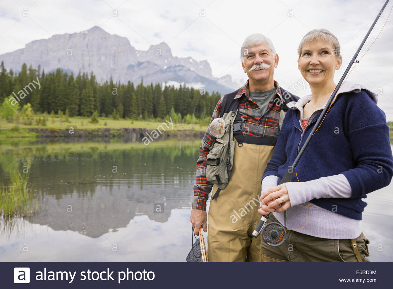 Older couple fishing in still lake Stock Photo