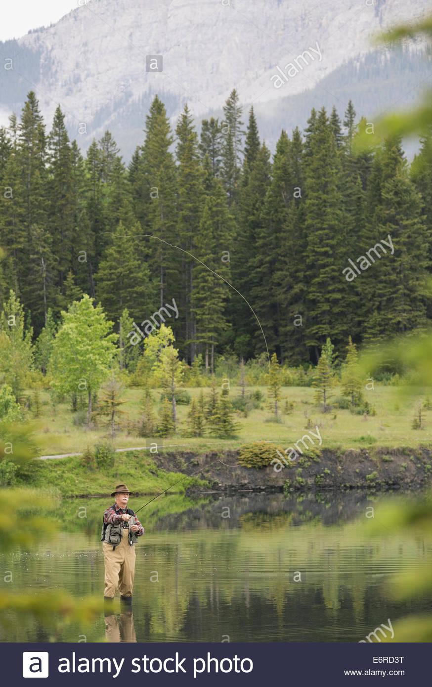 Older man fishing in still lake - Stock Image
