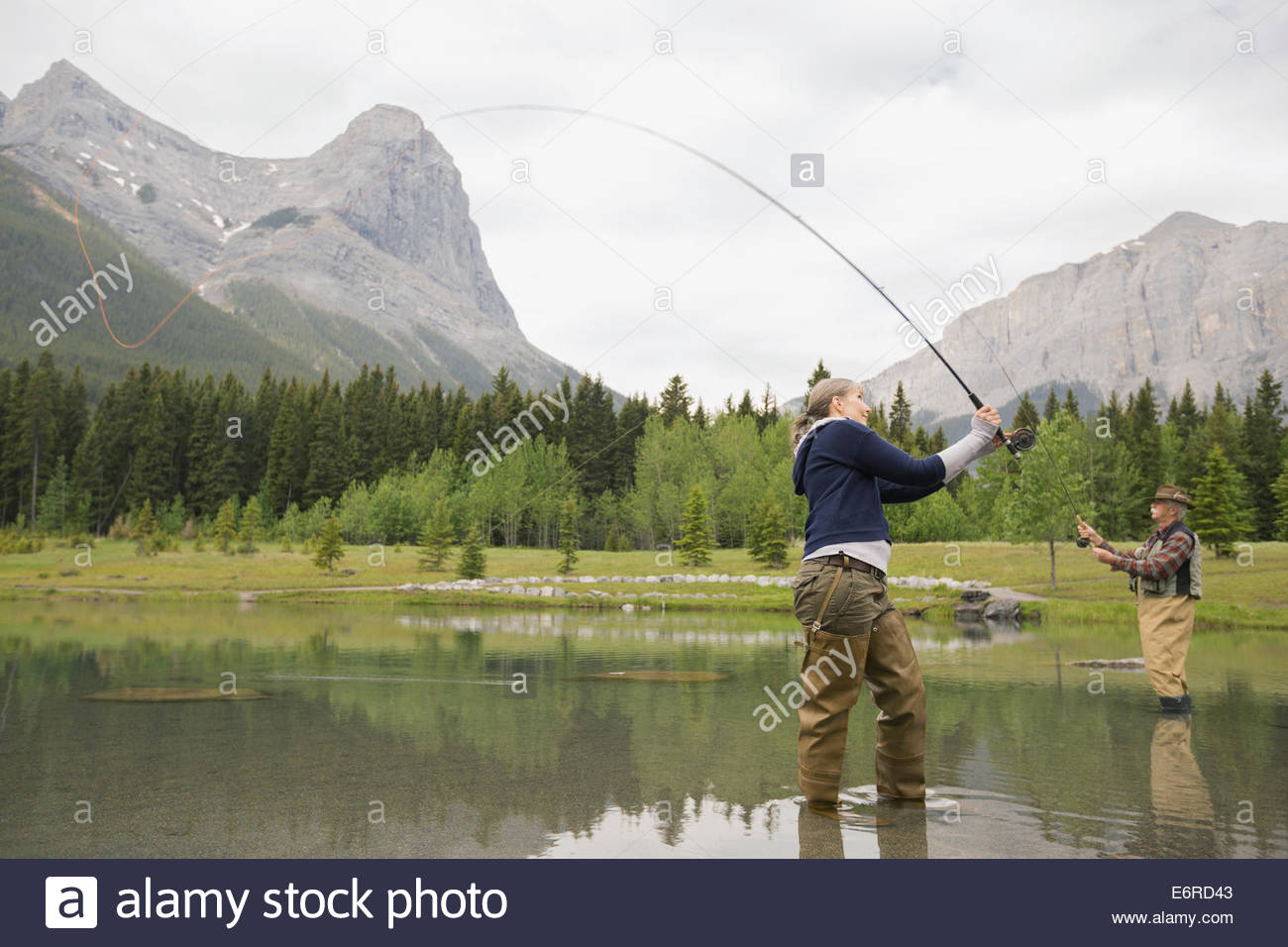 Older couple fishing in still lake - Stock Image