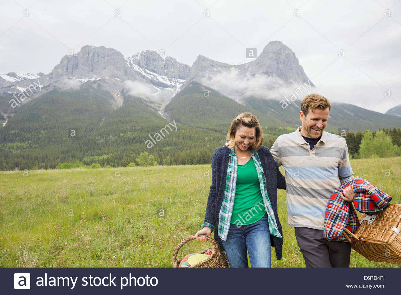 Couple having picnic in rural field - Stock Image