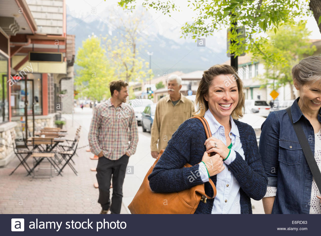 Couples walking on village street - Stock Image