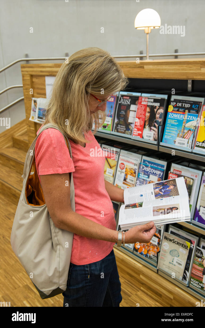 Reader in The Eemhuis in Amersfoort, Netherlands. The building is a cultural centre that combining a library, the - Stock Image