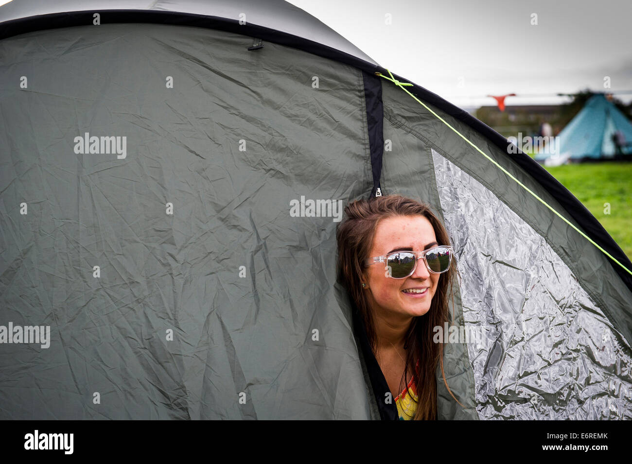 Stow Maries, UK. 29th August 2014. A young female festivalgoer peeps out of her tent at the Brownstock festival. Stock Photo