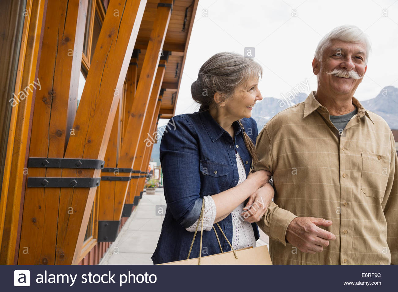Older couple walking on village street - Stock Image
