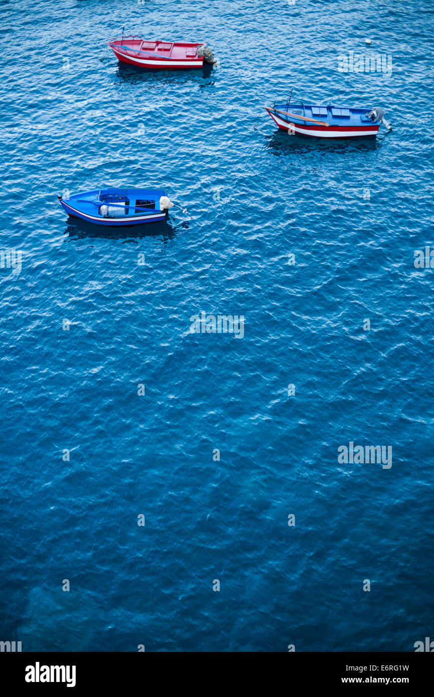 Three small fishing boats with oars and outboard motors are anchored in the bay of Câmara de Lobos. - Stock Image