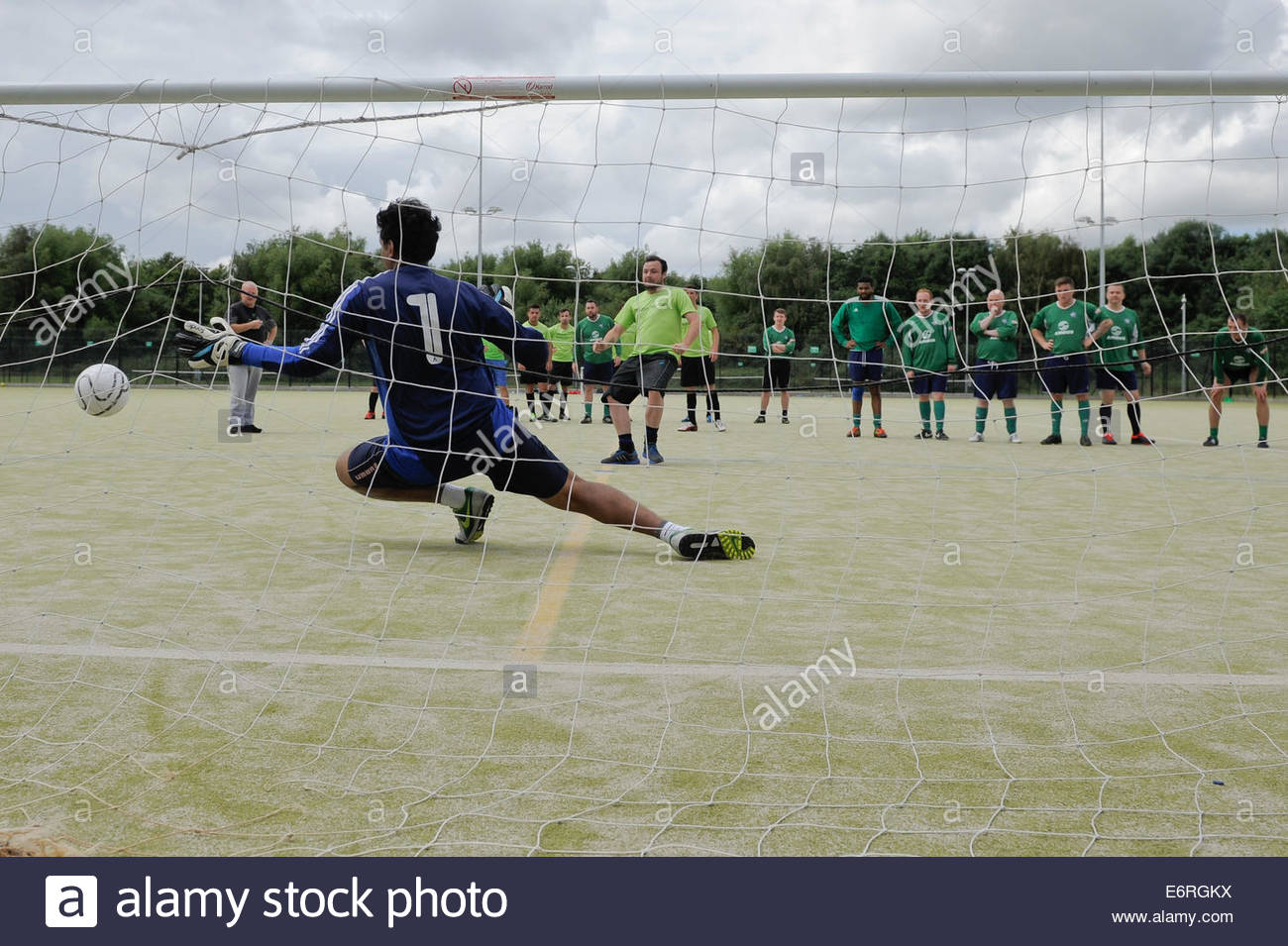 A goalkeepers view of a soccer match as a penalty kick is taken - Stock Image