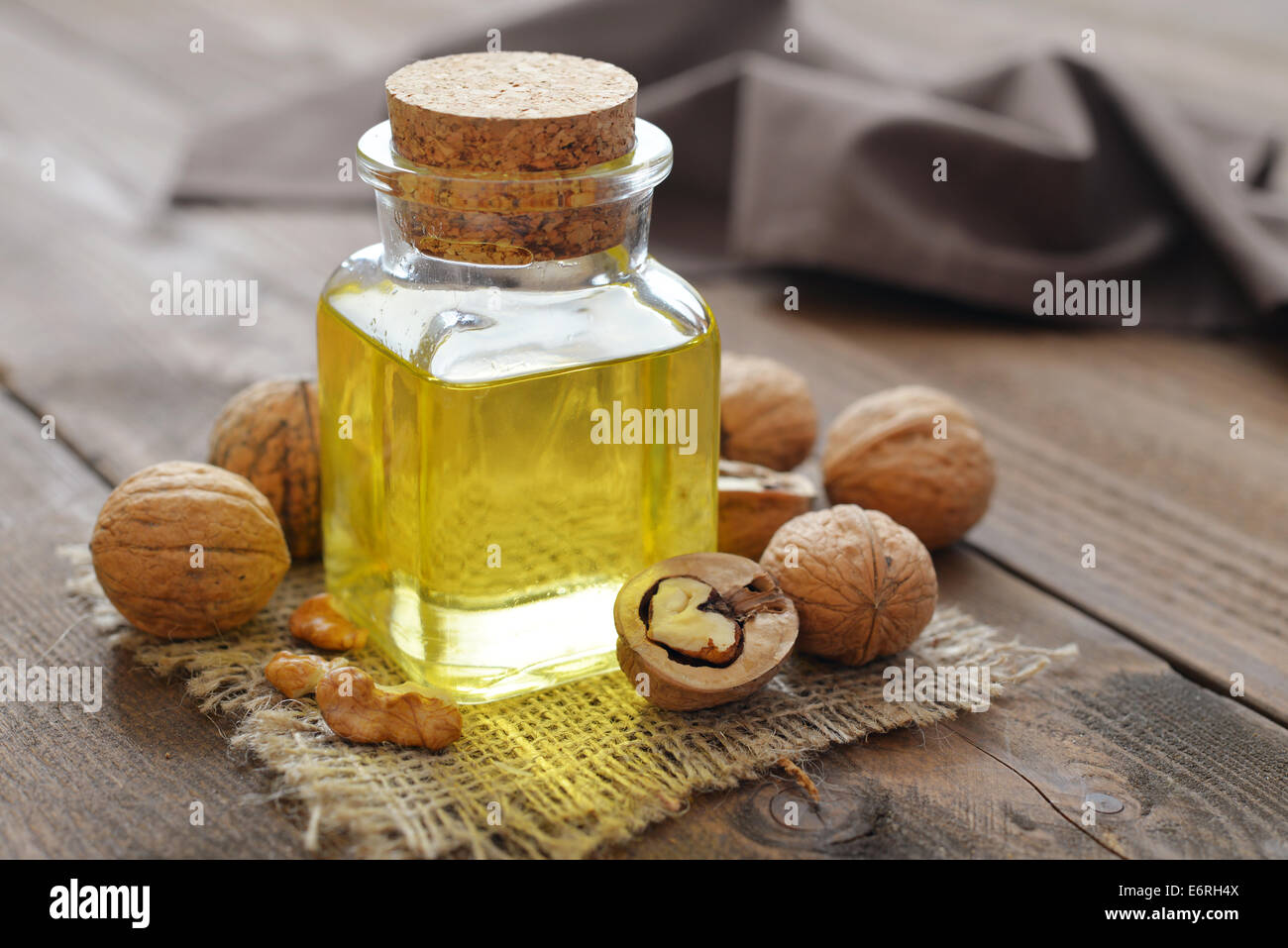 Walnut oil with nuts on a wooden background Stock Photo