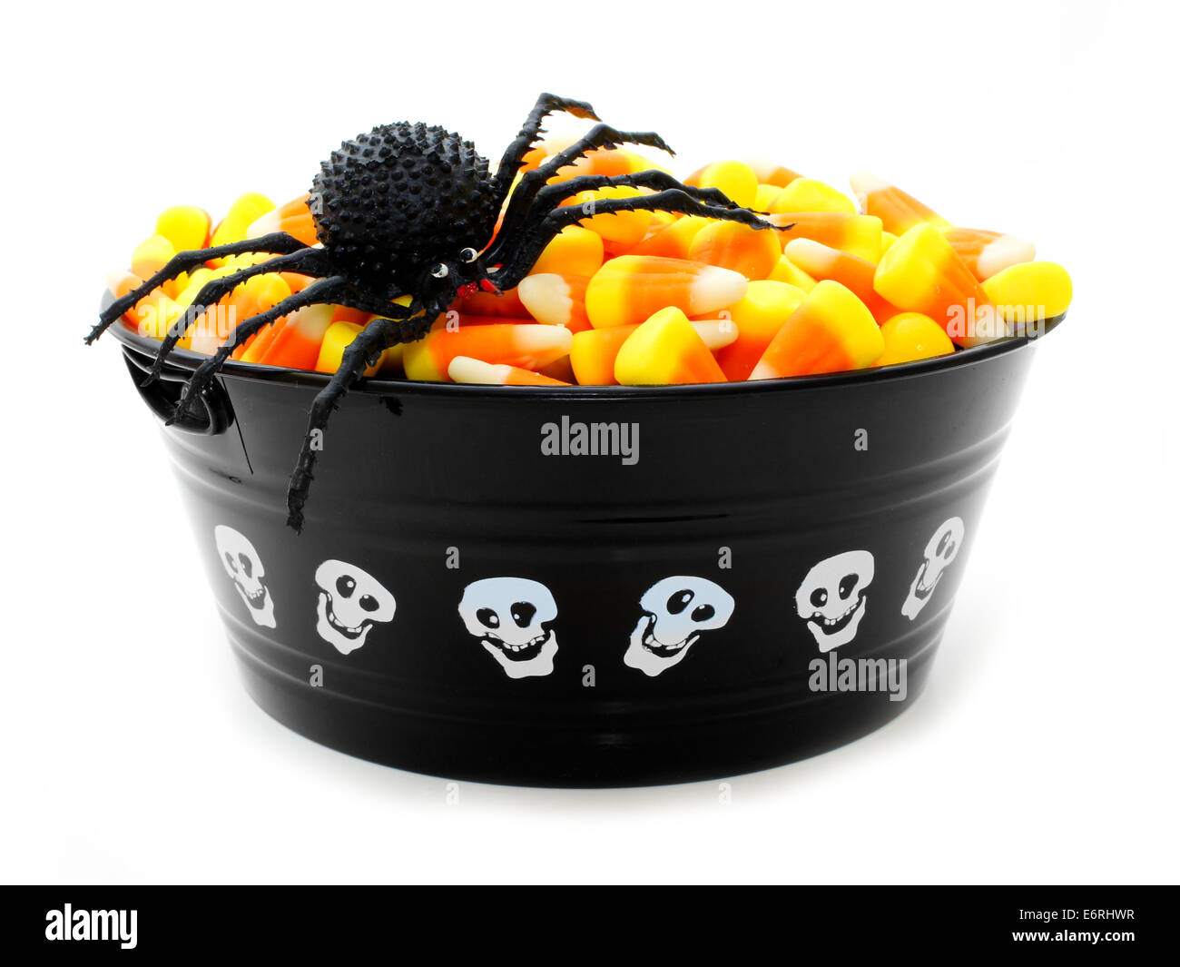 Halloween bowl filled with candy corn and toy spider isolated on white - Stock Image