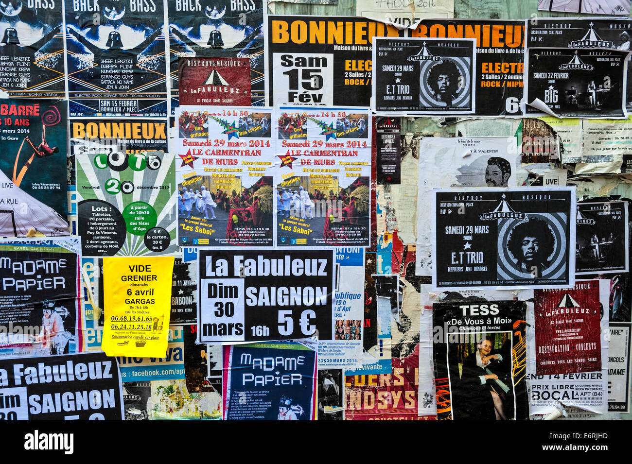The shutters of an abandoned French shop, covered with posters advertising concerts and sales - Stock Image