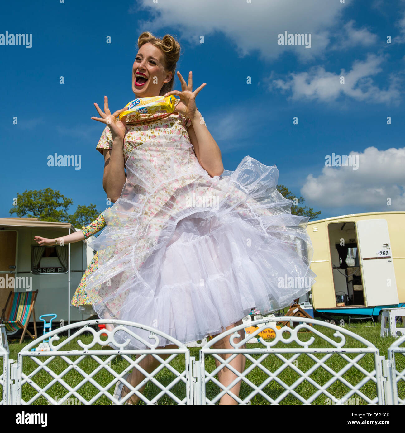 A woman dressed in retro 50's American housewife style summer dress frock standing outside her camper caravan - Stock Image