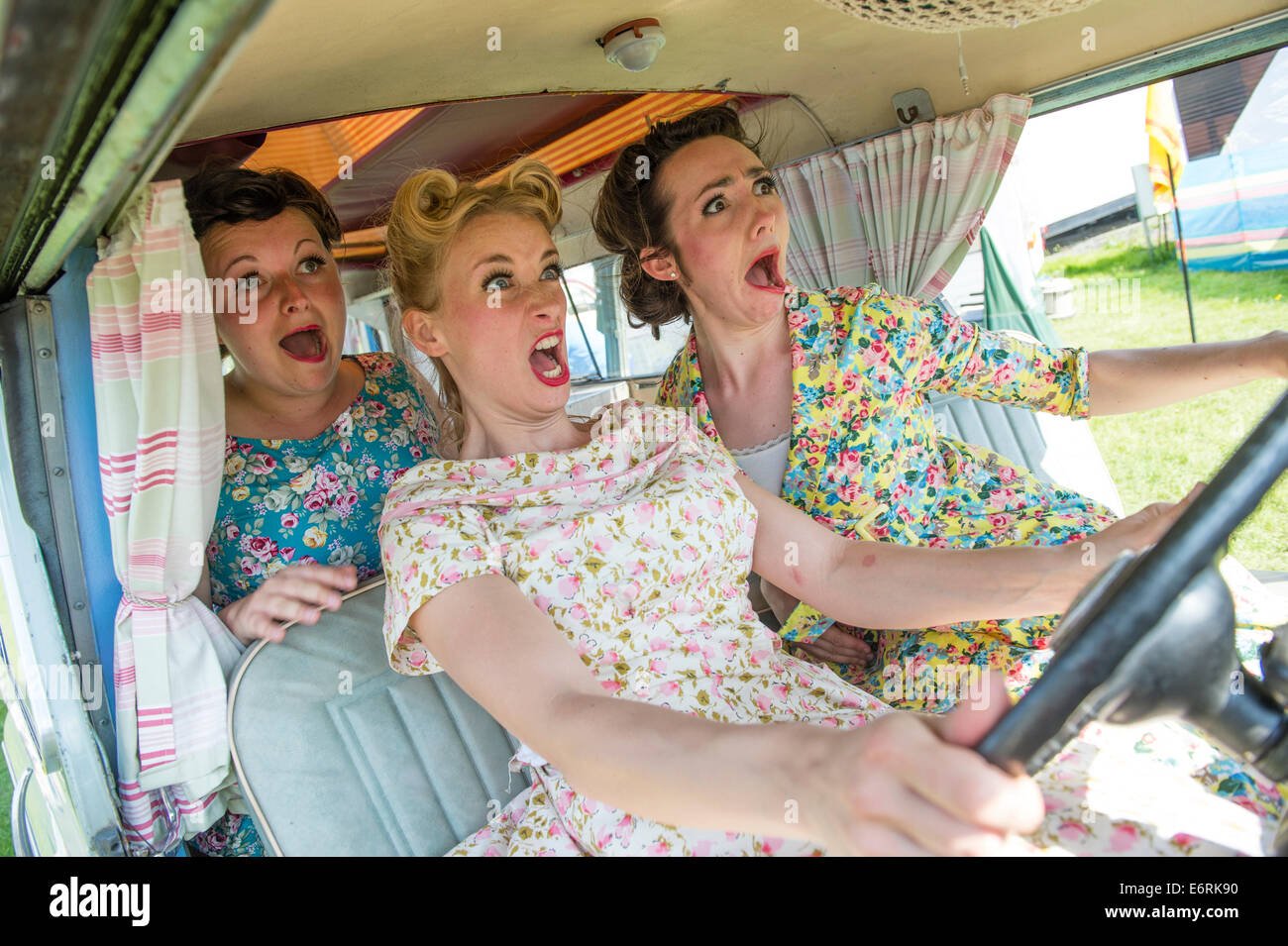 Three women dressed in retro 50's American housewife style summer dress frocks about to crash  in a camper van - Stock Image