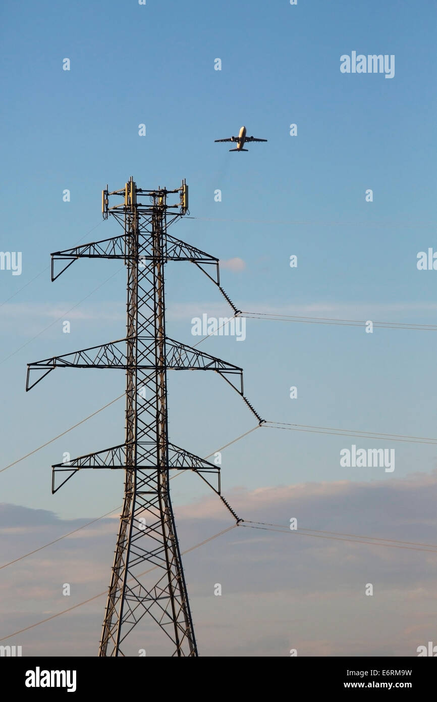 Plane flying past transmission tower. - Stock Image