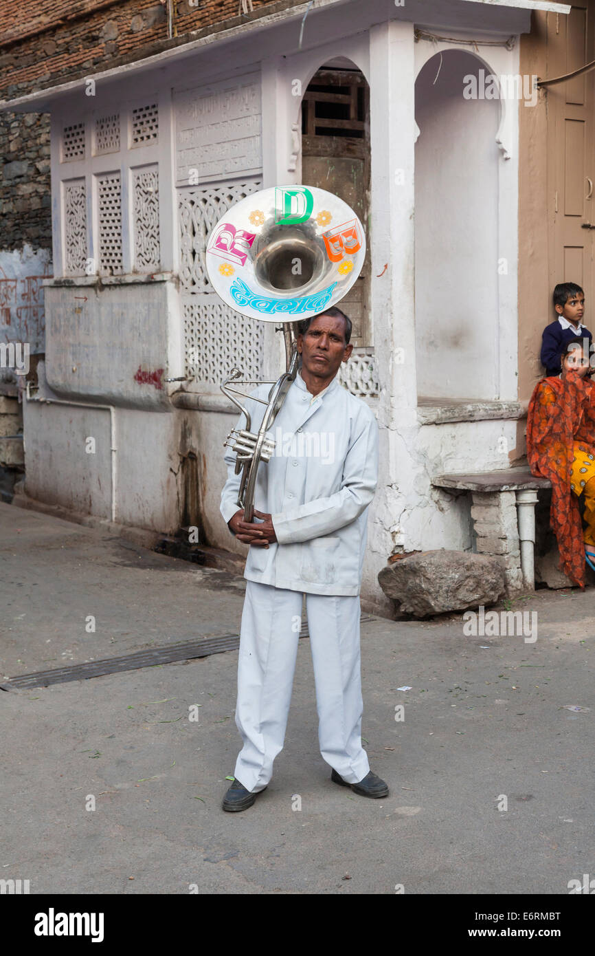 Local Indian musician with traditional large horn musical instrument, hired for a wedding procession, Deogarh, Rajasthan, - Stock Image