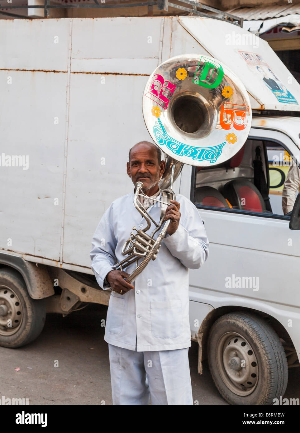 Local Indian musician with large horn musical instrument, hired for a wedding procession, Deogarh, Rajasthan, India - Stock Image