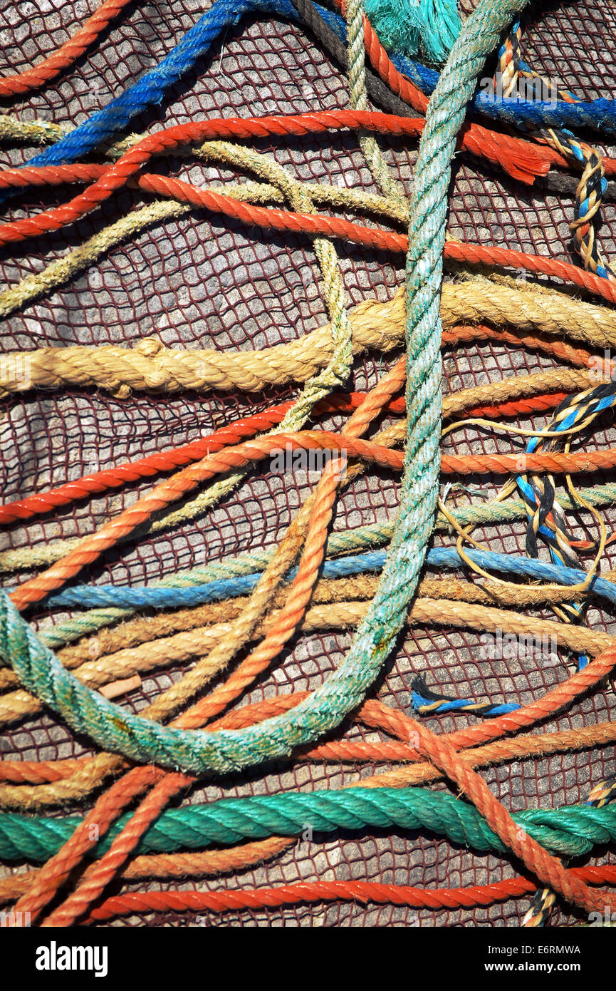 Messy background of colorful old fishing nets and ropes under sunlight - Stock Image