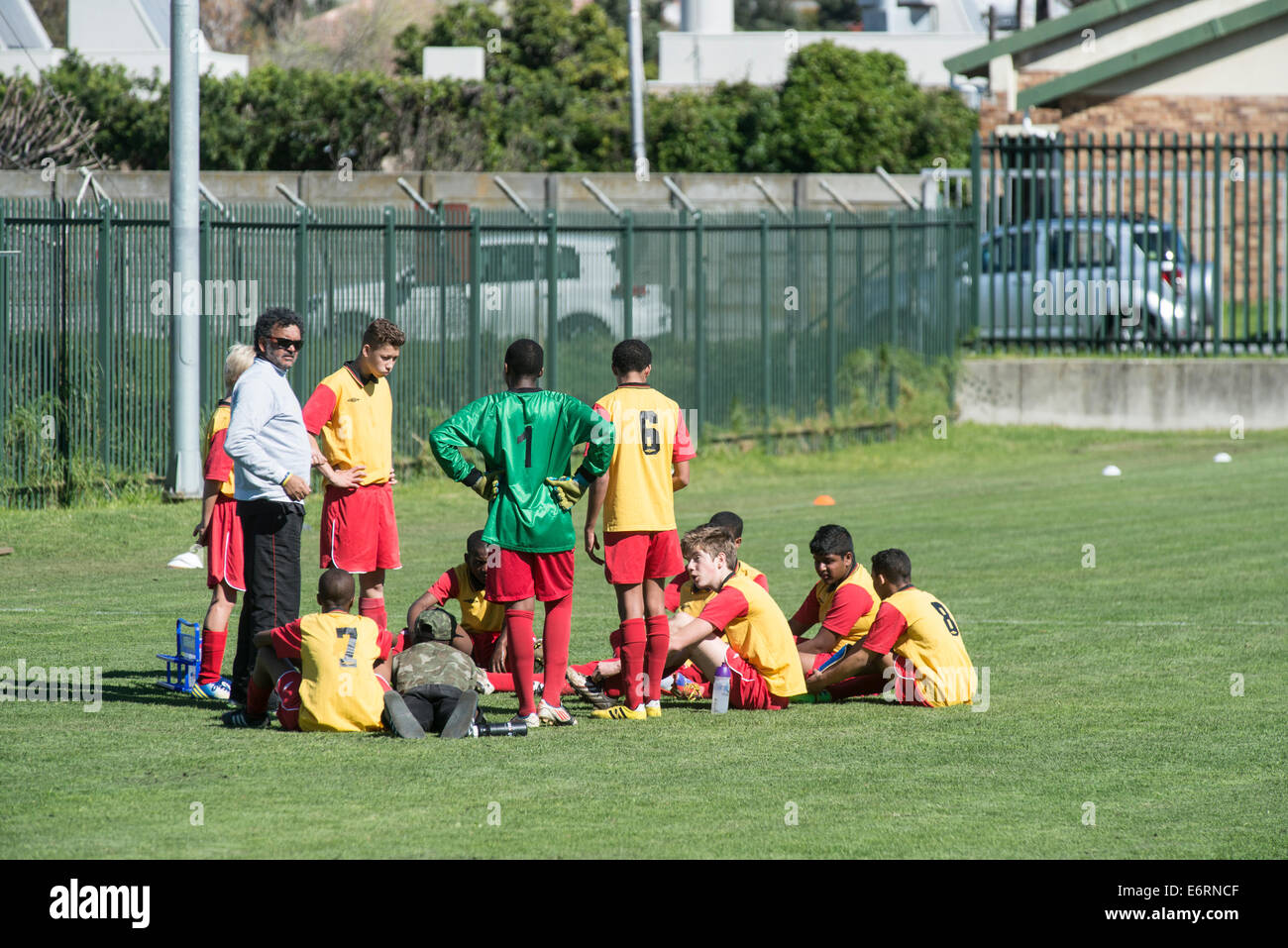 Coach and U15 football team during half time break, Cape Town, South Africa - Stock Image