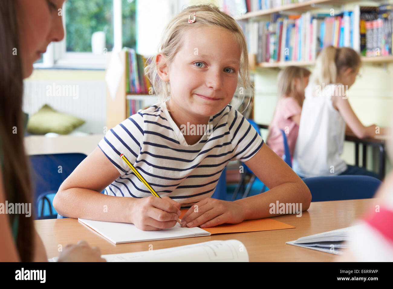 Elementary School Pupil Working At Desk In Classroom - Stock Image
