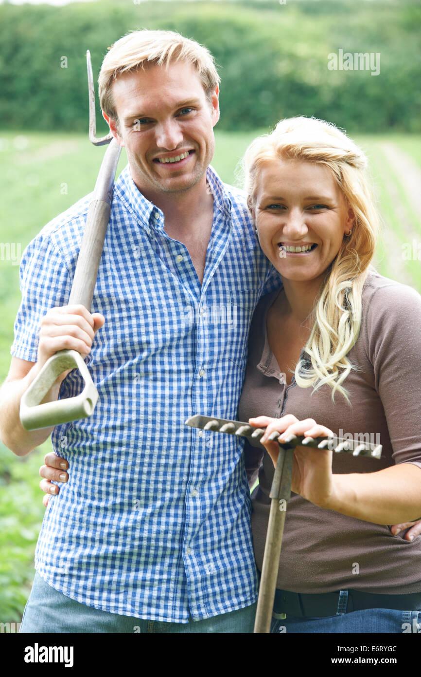 Portrait Of Couple Working On Organic Farm - Stock Image