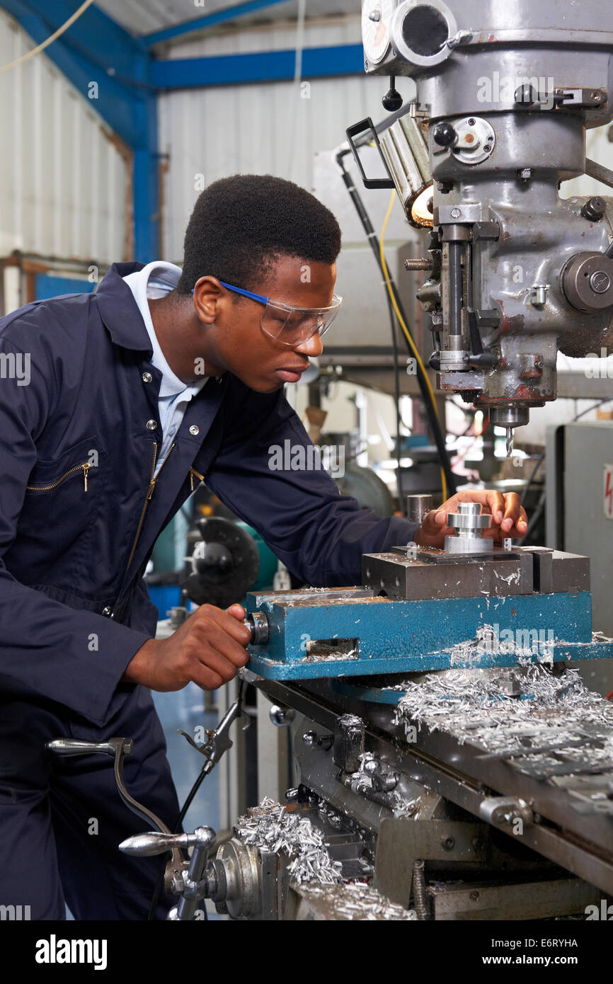 Male Apprentice Engineer Working On Drill In Factory - Stock Image