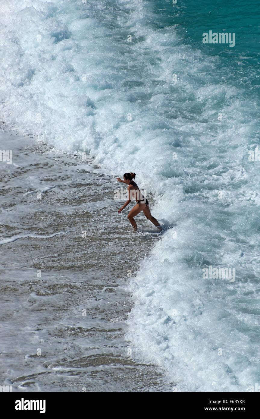 Frau flieht vor einer Welle Stock Photo