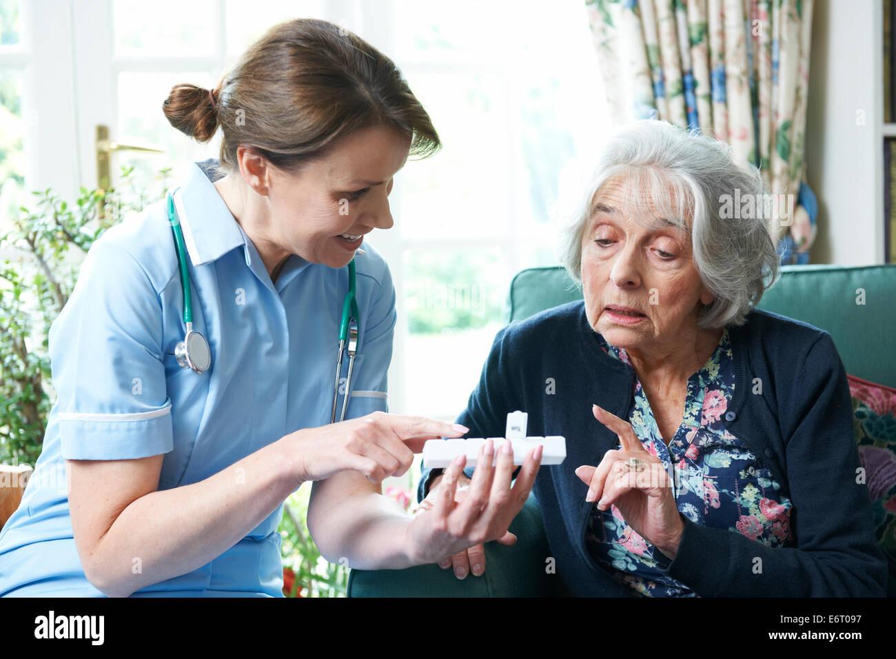 Nurse Advising Senior Woman On Medication At Home Stock Photo