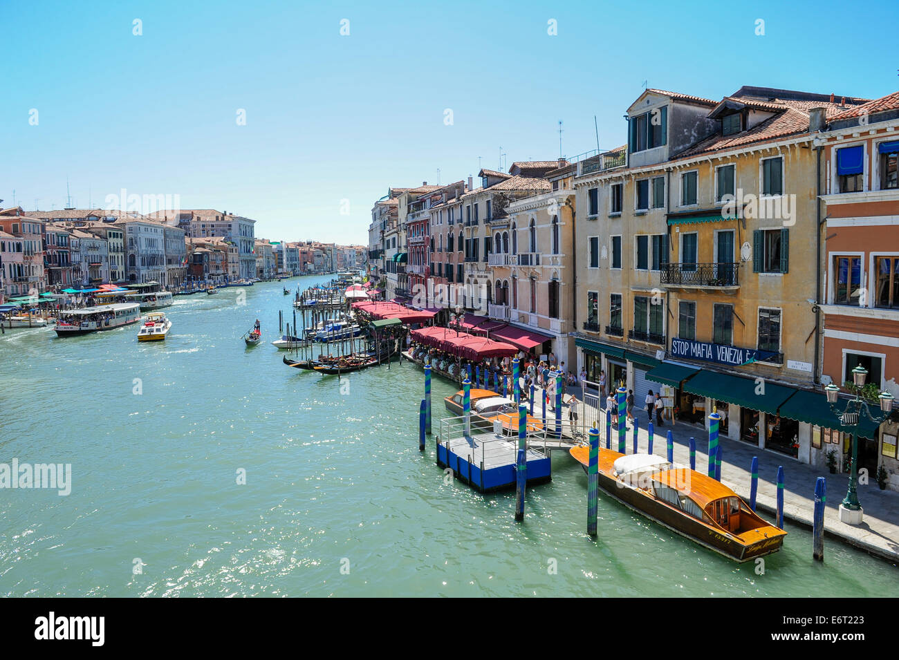 Boats, gondolas and tourists along the grand canal and a sign, stop the Mafia in Venice. - Stock Image
