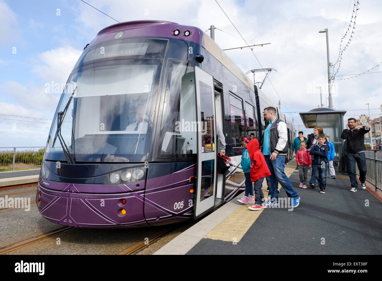 Passengers clamber aboard one of the newest additions to Blackpool's tram fleet - Stock Image
