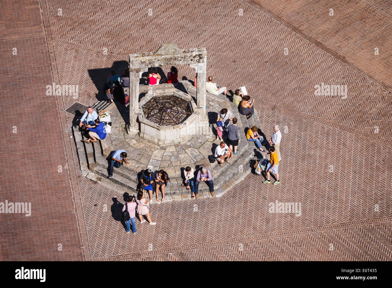 Aerial View Of People Sitting Around The Medieval Well In Piazza Della Cisterna San Gimignano Tuscany Italy