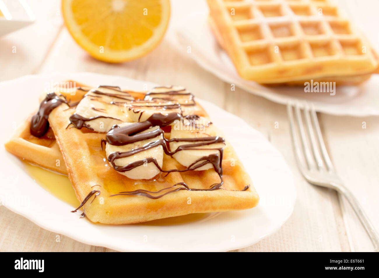 Sweet waffels and banana slices with melted chocolate.selective focus on the front waffels - Stock Image
