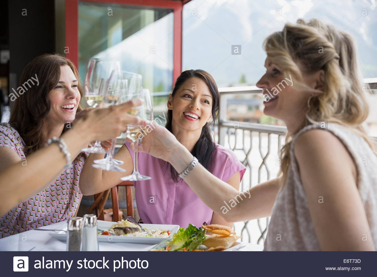 Women toasting each other in restaurant - Stock Image