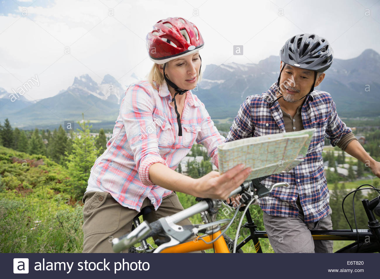 Couple on mountain bikes reading map on hillside - Stock Image