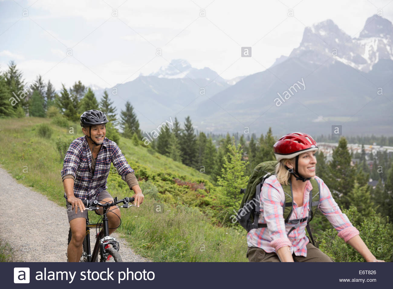 Couple riding mountain bikes on hillside - Stock Image