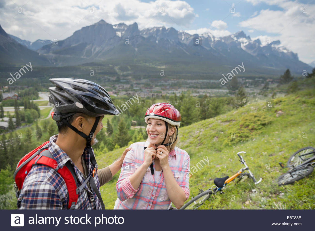 Couple with mountain bikes on hillside - Stock Image