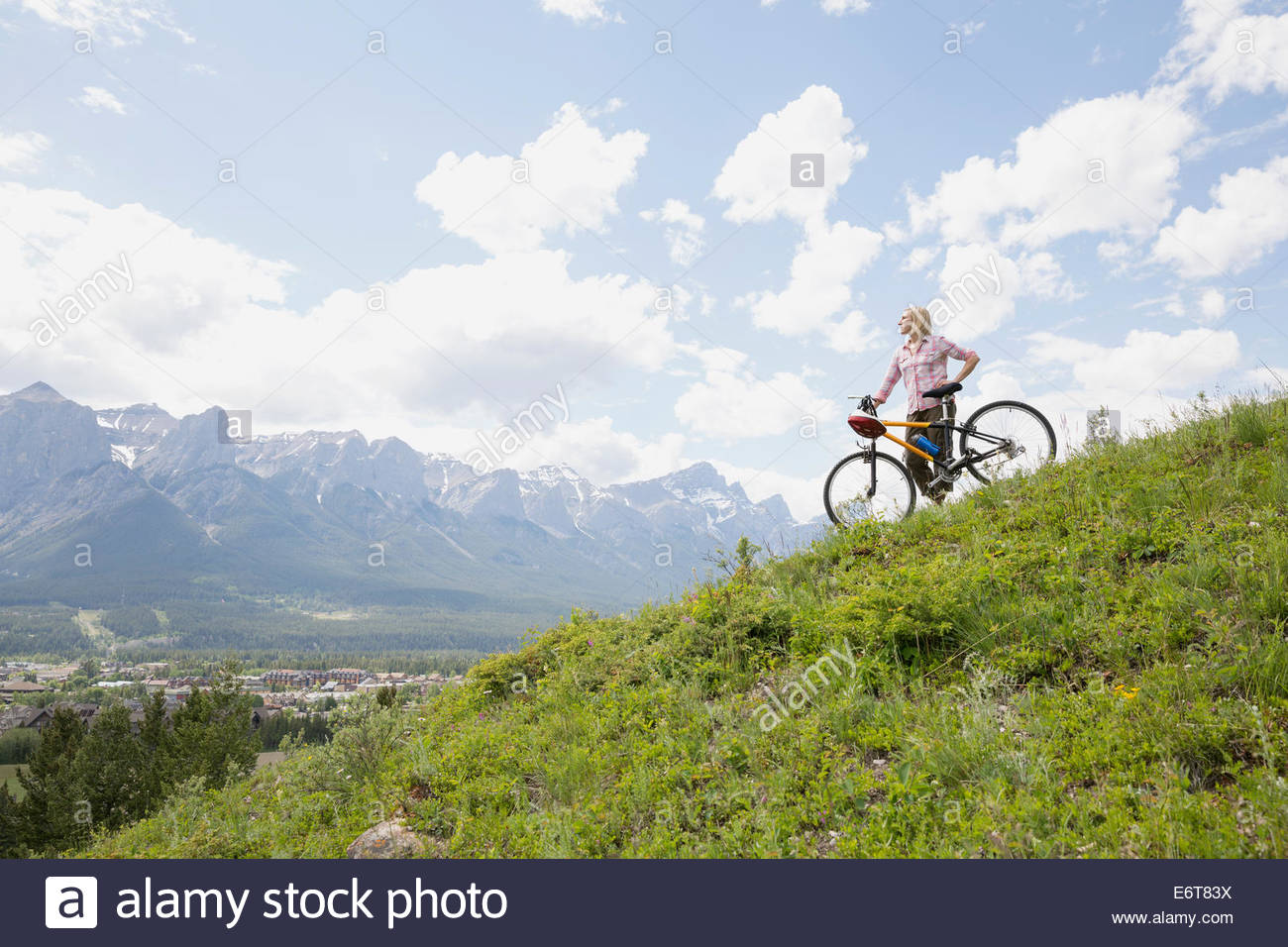 Woman standing with mountain bike on hillside - Stock Image