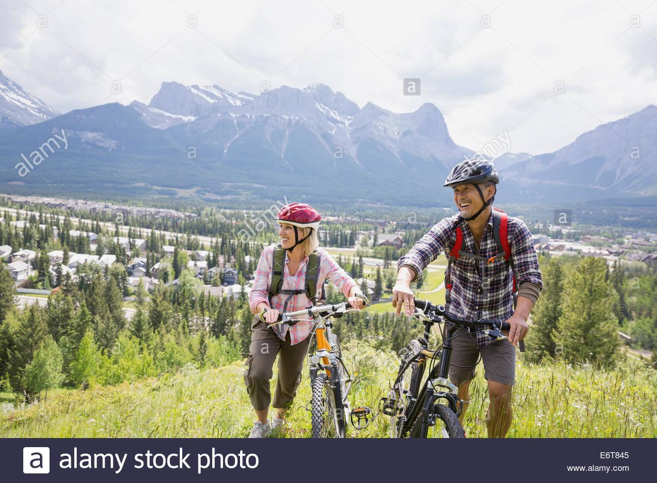 Couple walking with mountain bikes on hillside - Stock Image