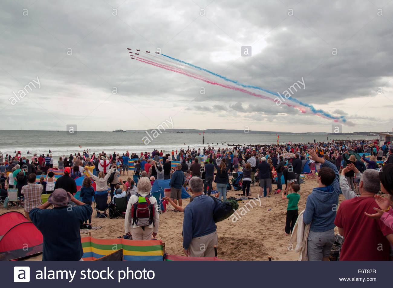 Bournemouth, UK, 30th August 2014: The crowd cheers and waves as the RAF Red Arrows team of eight planes perform - Stock Image