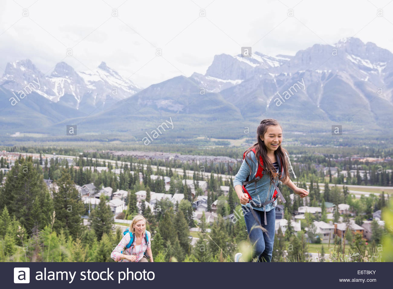 Mother and daughter hiking on rural hillside - Stock Image