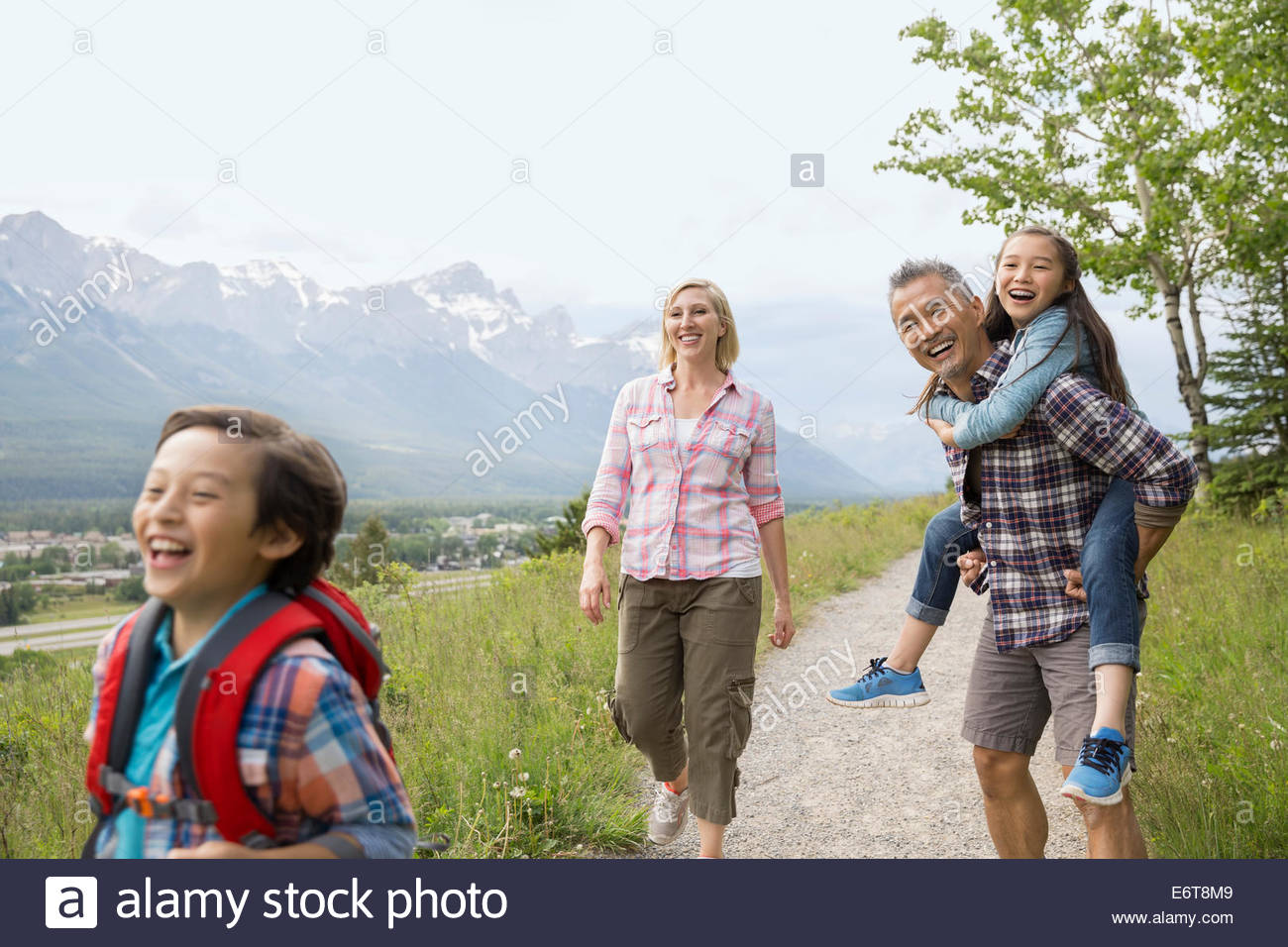 Parents and daughter walking on dirt path - Stock Image