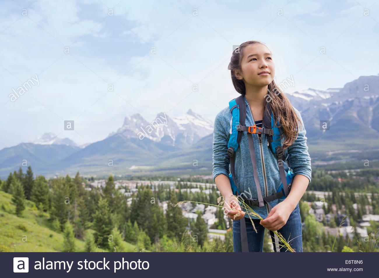 Girl examining plants on rural hillside - Stock Image