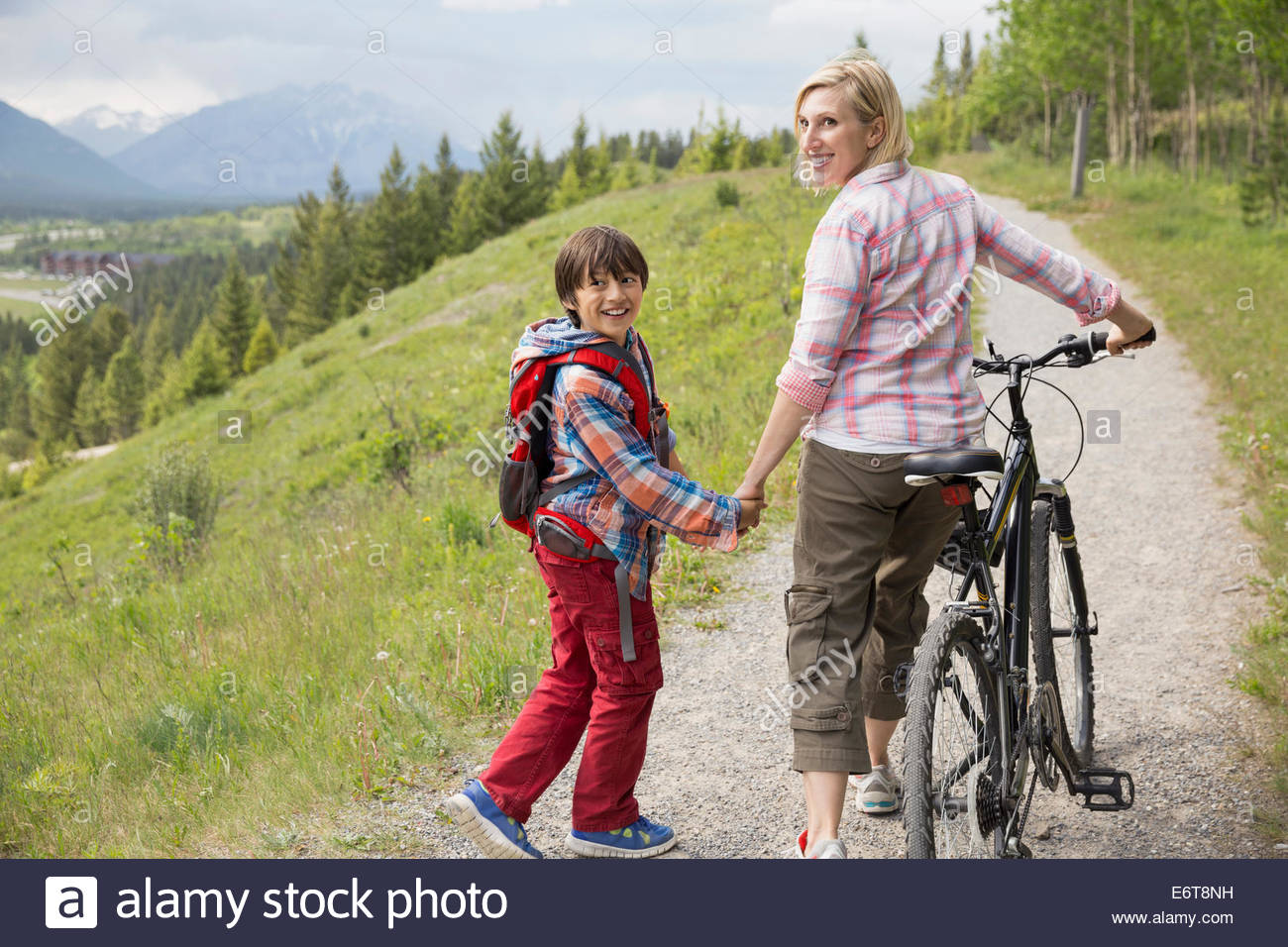 Mother and son walking on dirt path - Stock Image