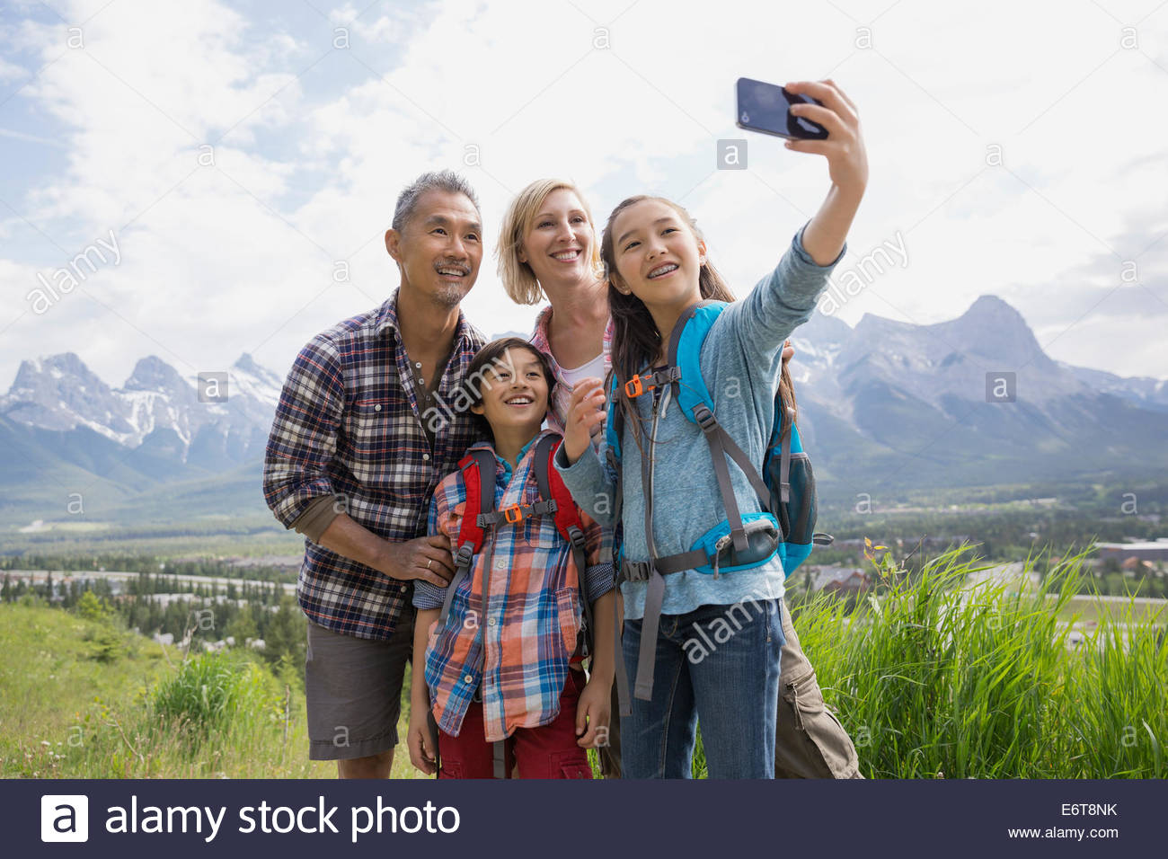 Family taking cell phone picture on rural hillside - Stock Photo