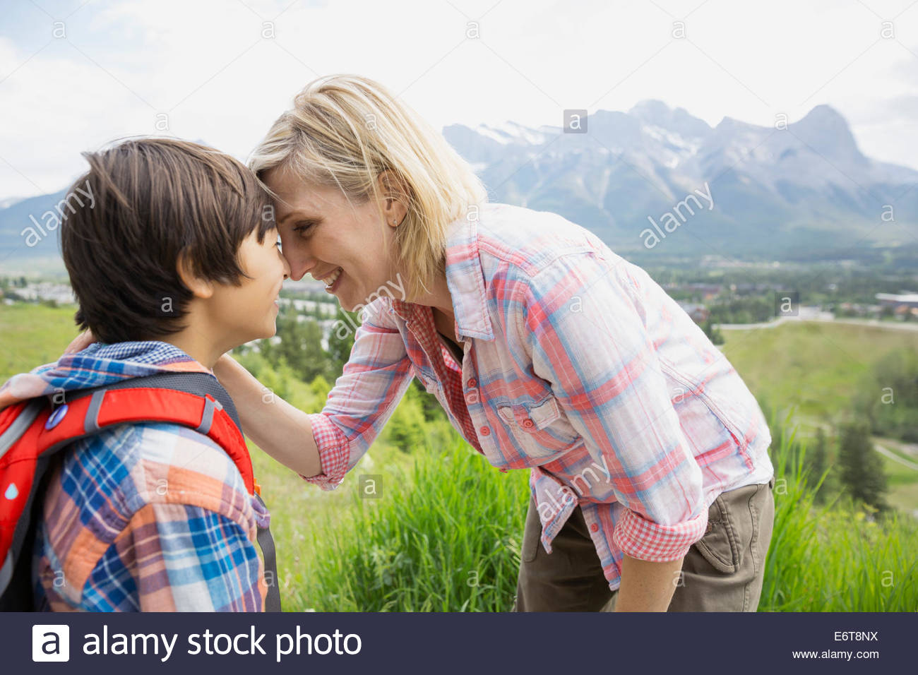 Mother and son touching noses on rural hillside - Stock Image