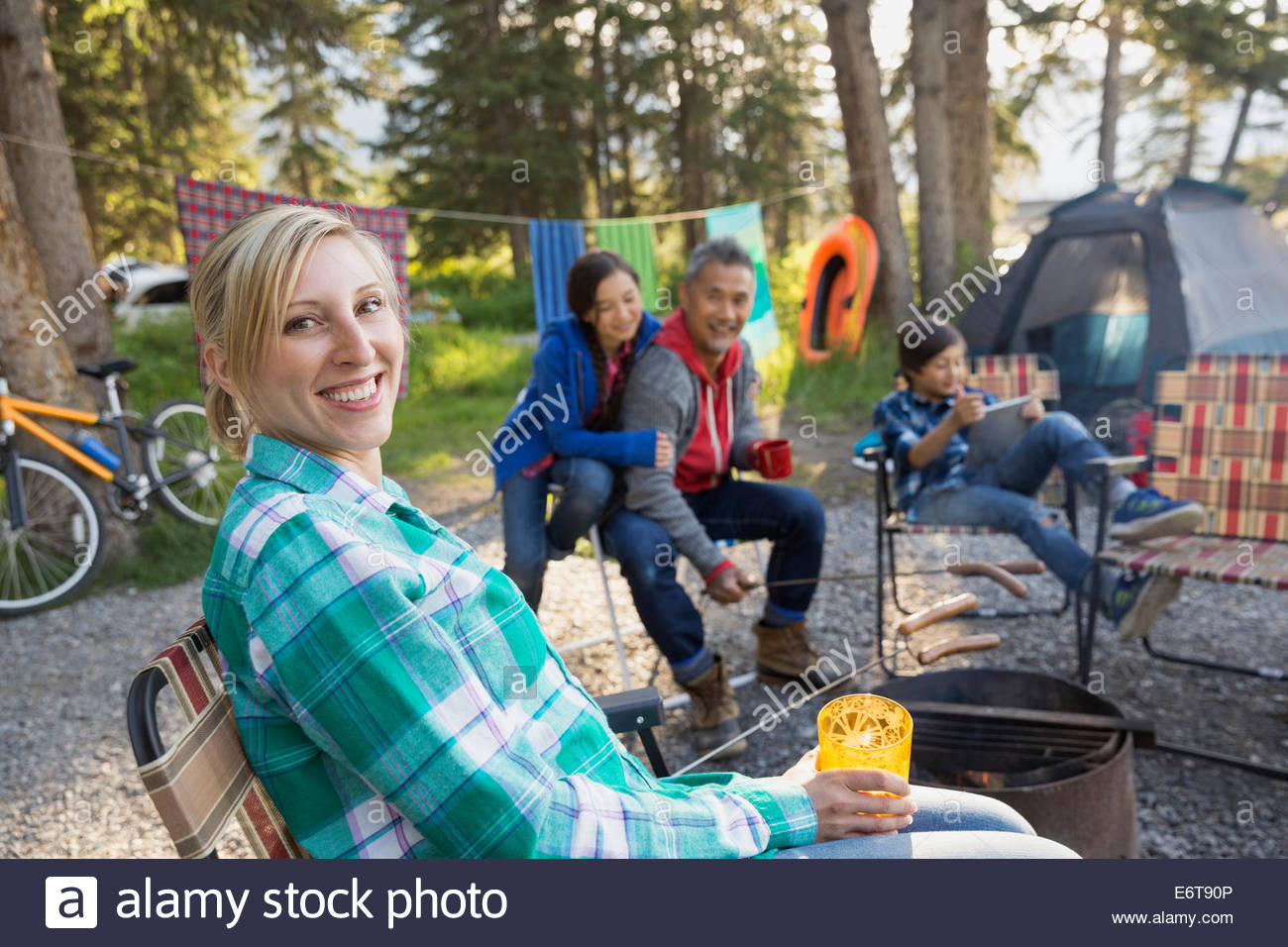 Family relaxing together around campfire - Stock Image