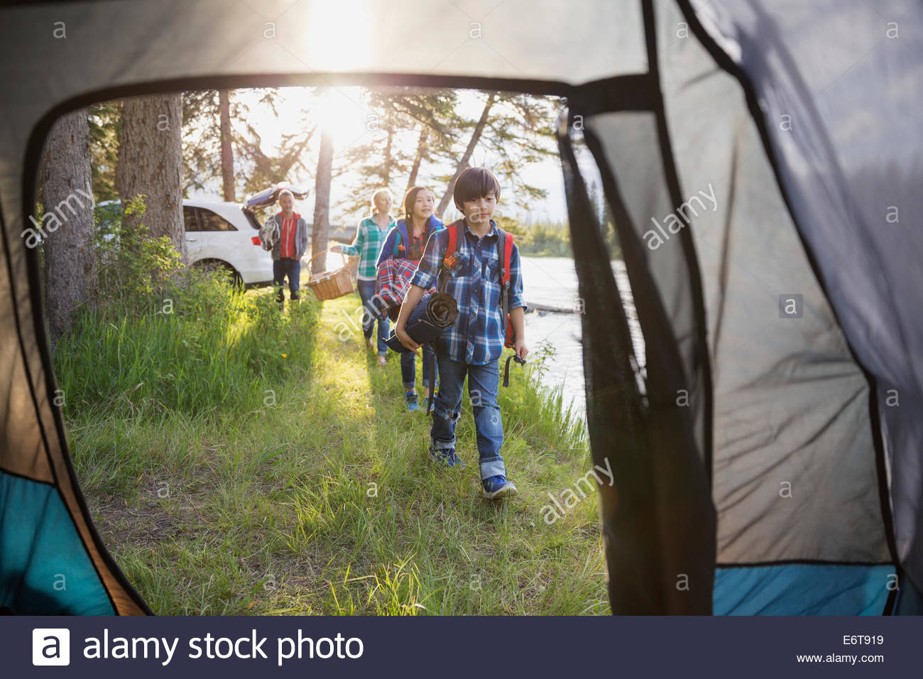 Family carrying gear at campsite - Stock Image