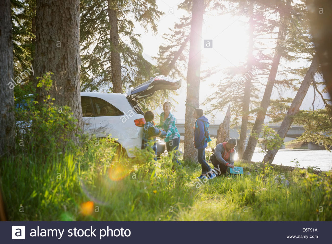 Family unpacking car at campsite - Stock Image