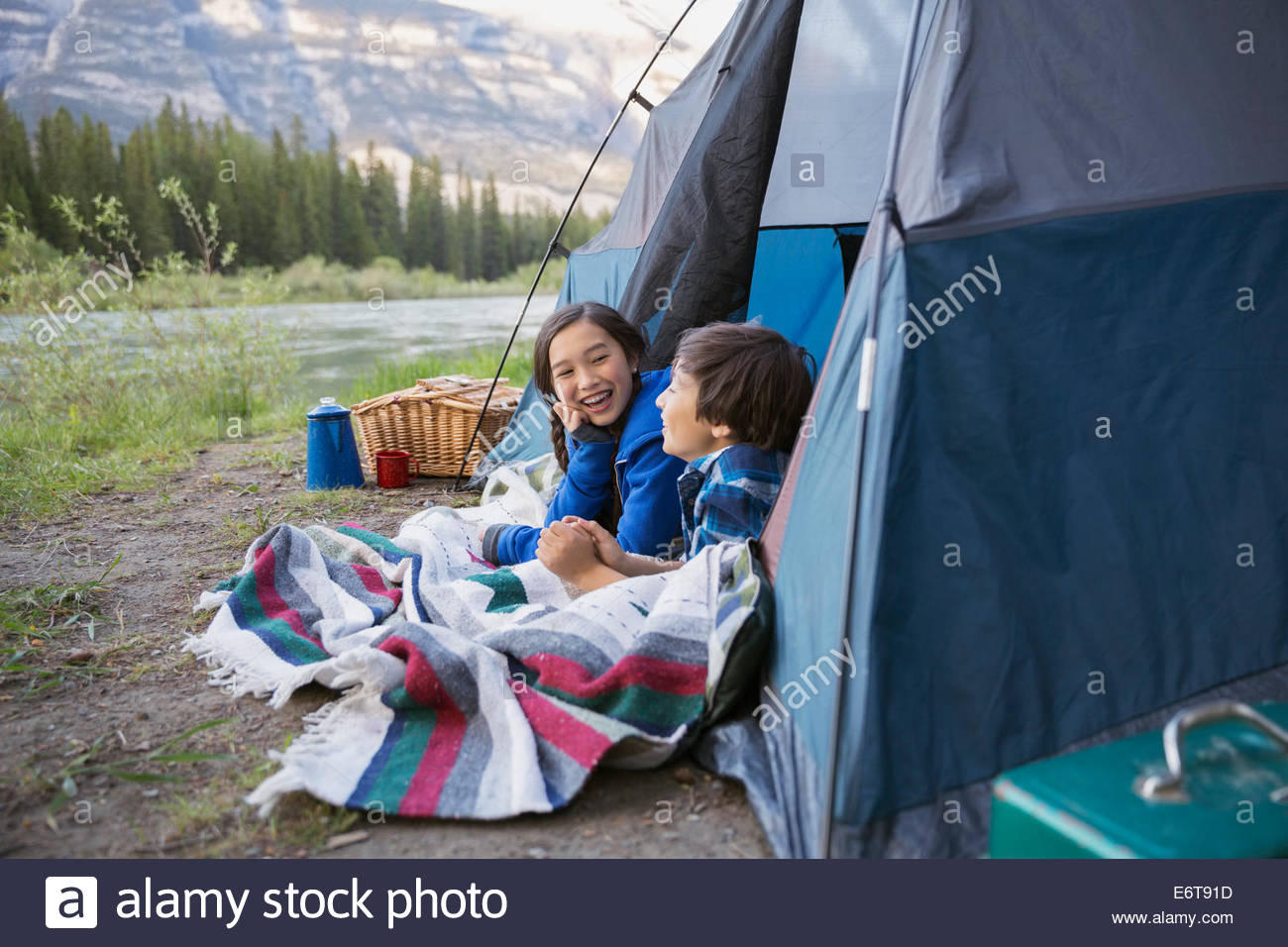 Children relaxing in tent at campsite - Stock Image