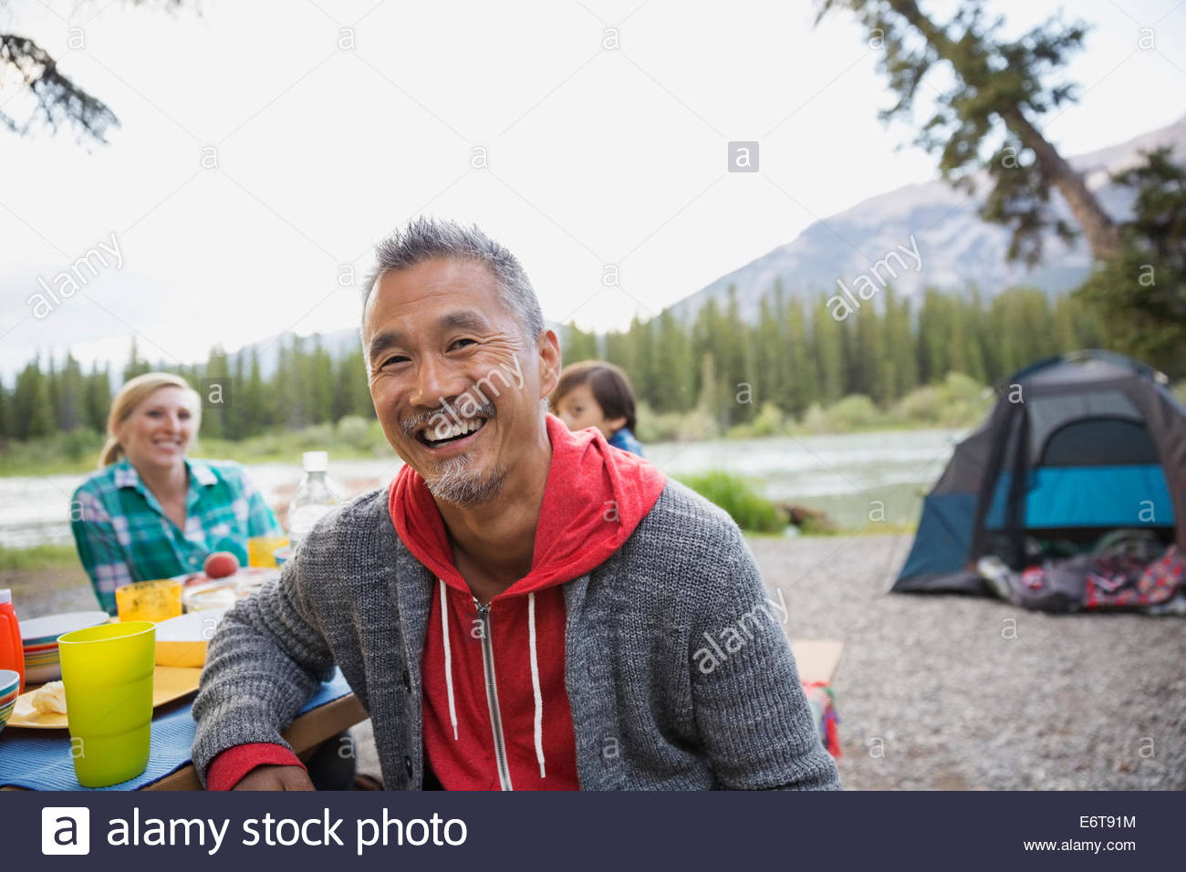 Man smiling at picnic table at campsite - Stock Image