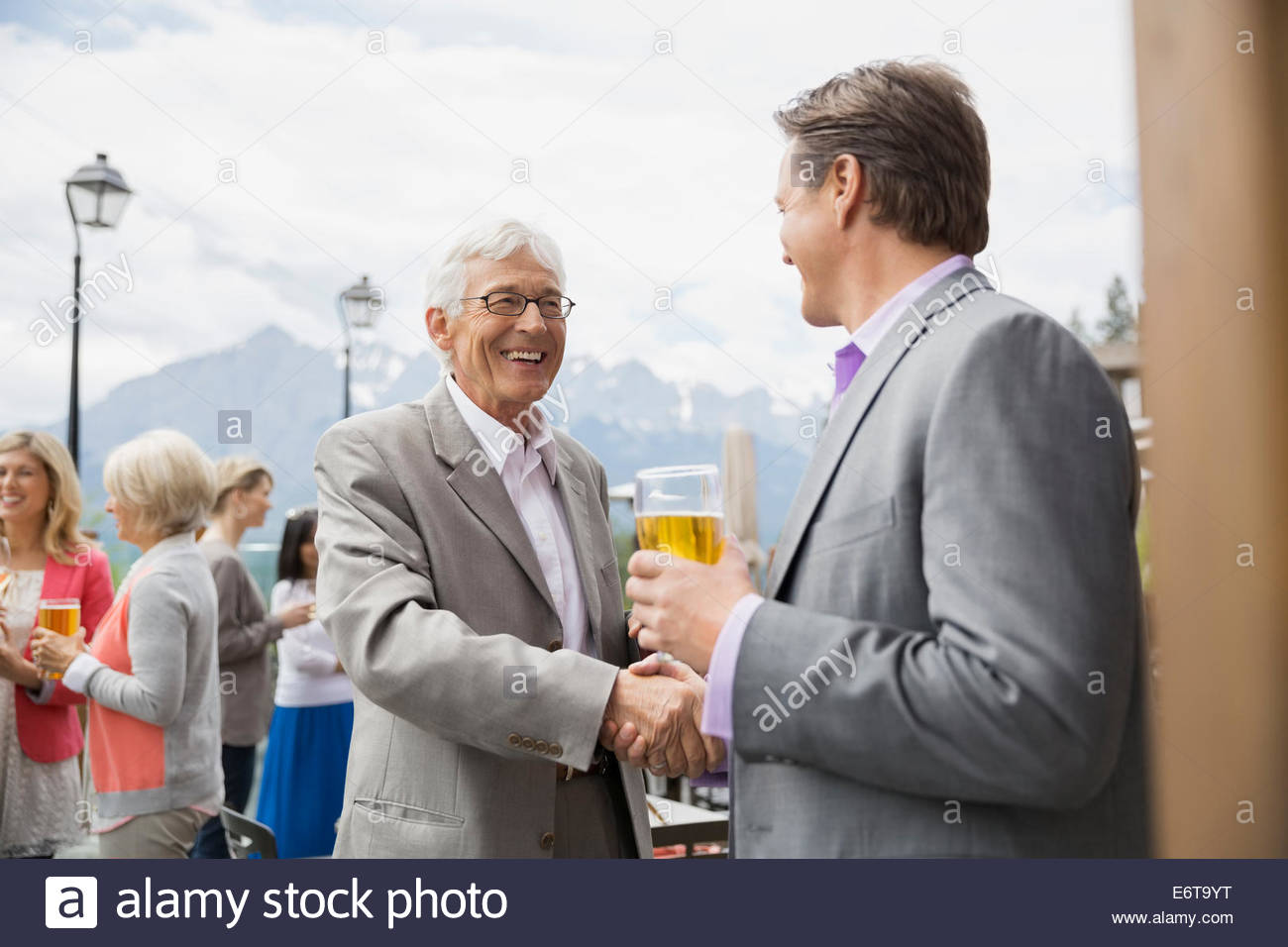 Businessmen shaking hands at networking event - Stock Image