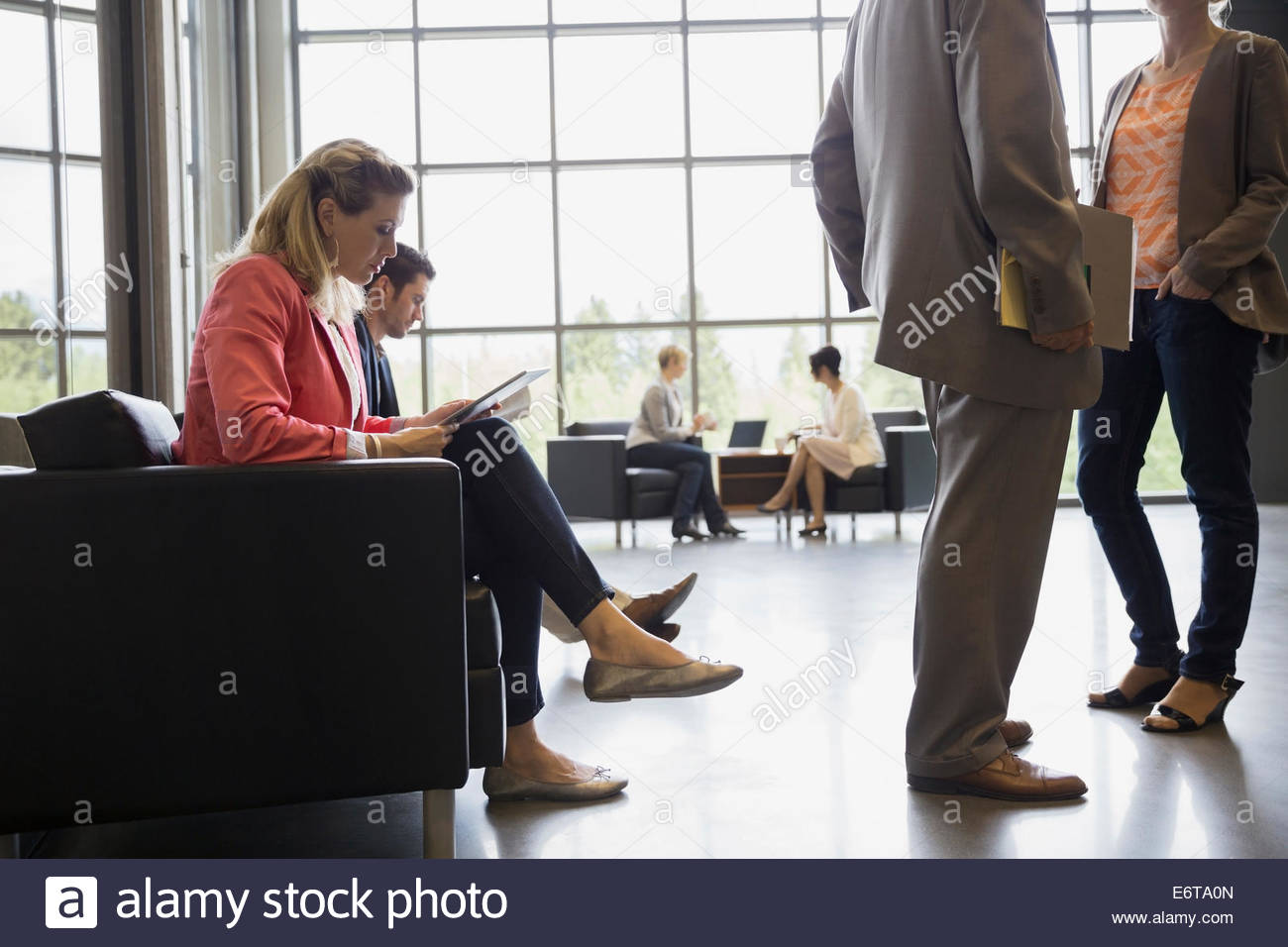 Business woman using digital tablet in office lobby Stock Photo