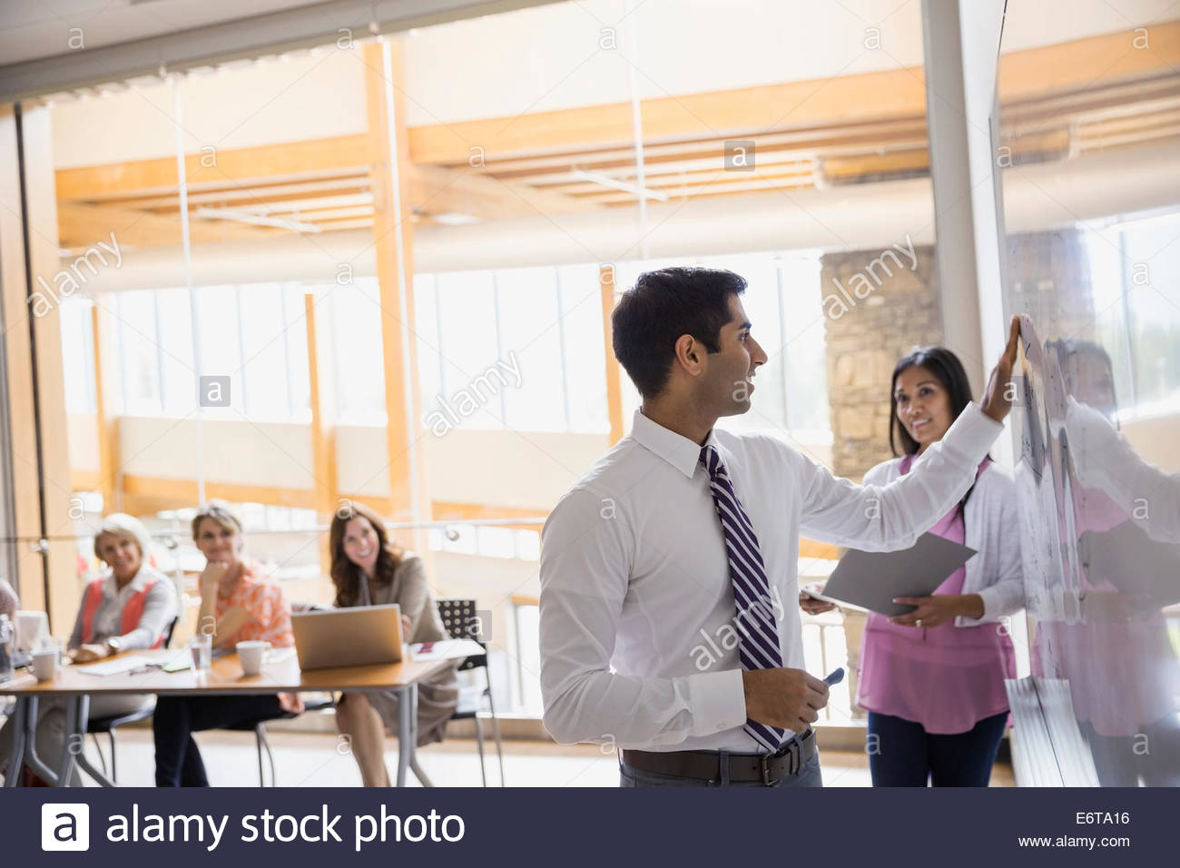 Businessman writing on white board in meeting - Stock Image